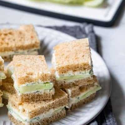 Cucumber sandwiches stacked on top of each other on plate