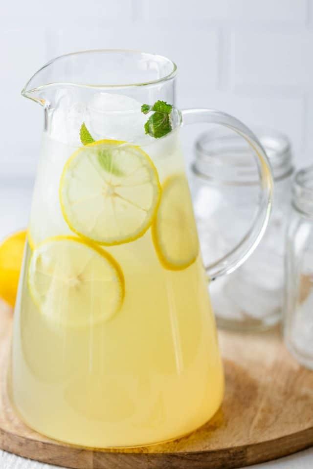 Clear jug of lemonade with fresh slices of lemons