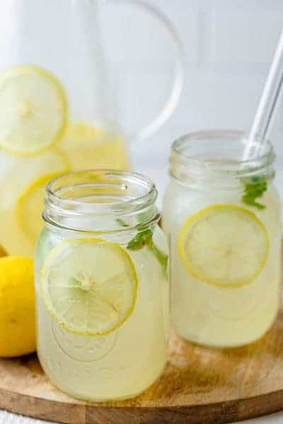 Homemade lemonade in a cup with glass jug in the background and lemons on the side