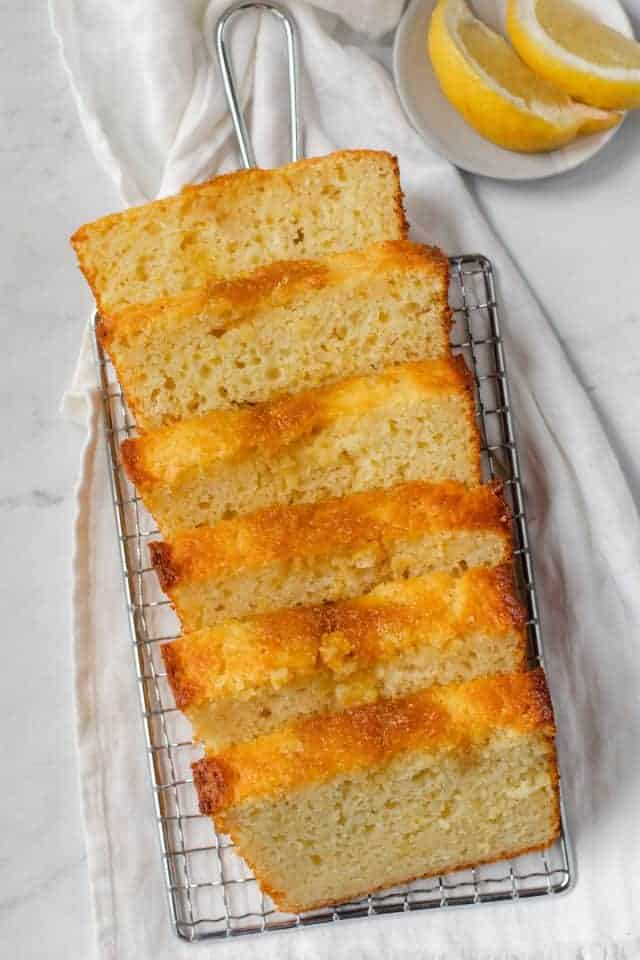 Lemon bread recipe sliced on a cooling rack with lemon wedges near by