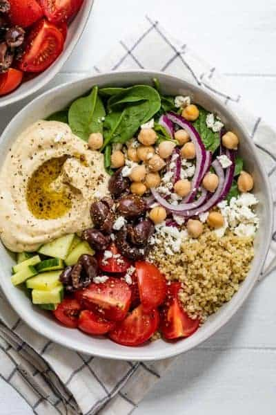 Close up of large full hummus bowl with cucumbers, tomatoes, quinoa, chickpeas, spinach, onions and feta cheese