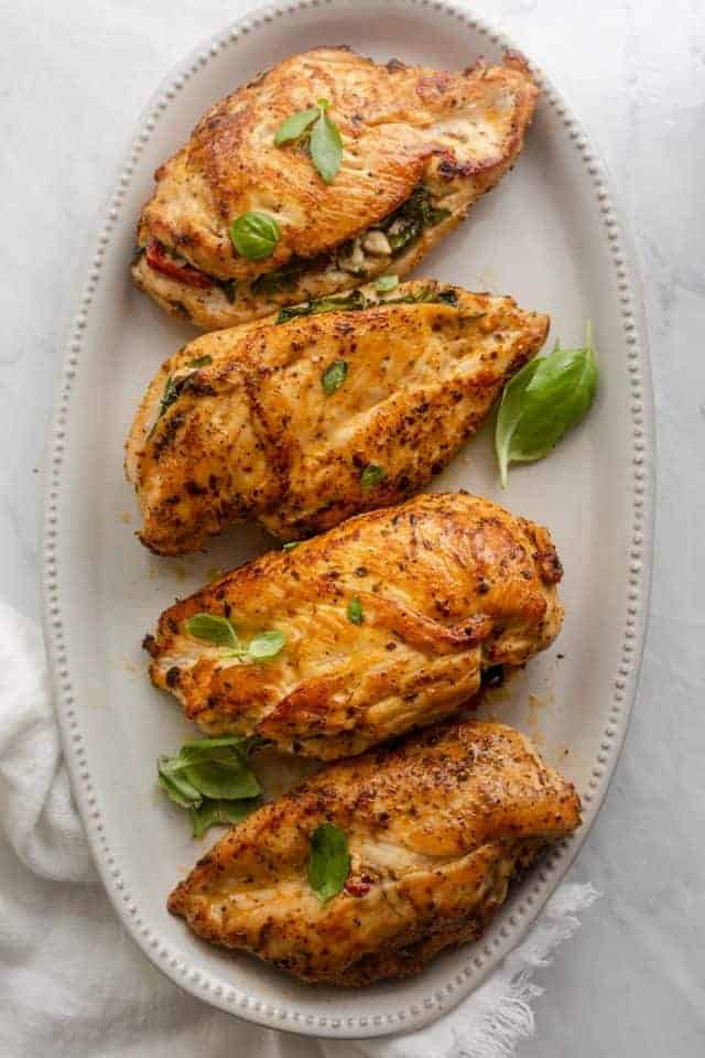 Mediterranean stuffed chicken on a long serving plate garnished with basil
