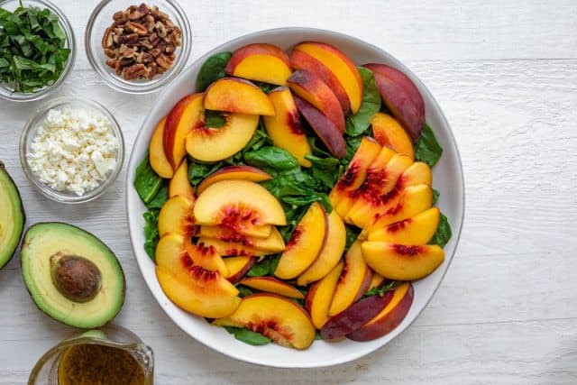 Large bowl of spinach and peaches with avocados, basil, pecans, feta cheese and dressing on the side