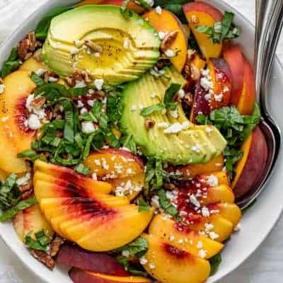 Large bowl of summer peach salad with spinach and avocado with large serving spoon inside