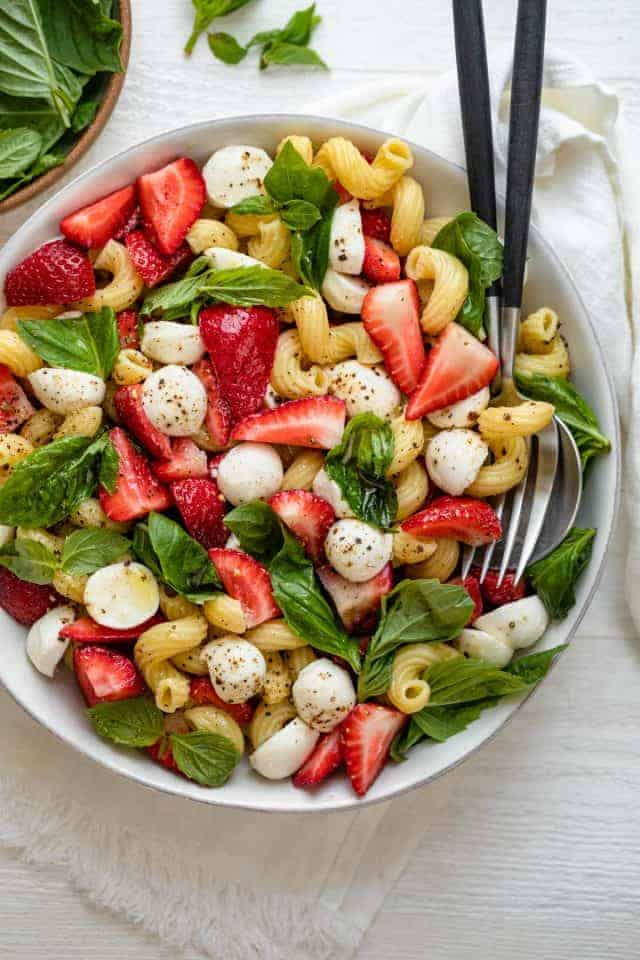 Strawberry caprese salad in large bowl with serving utensils in bowl