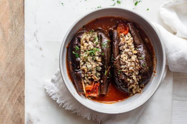 Two stuffed eggplant (mahshi) in a bowl cut open with stuffing showing