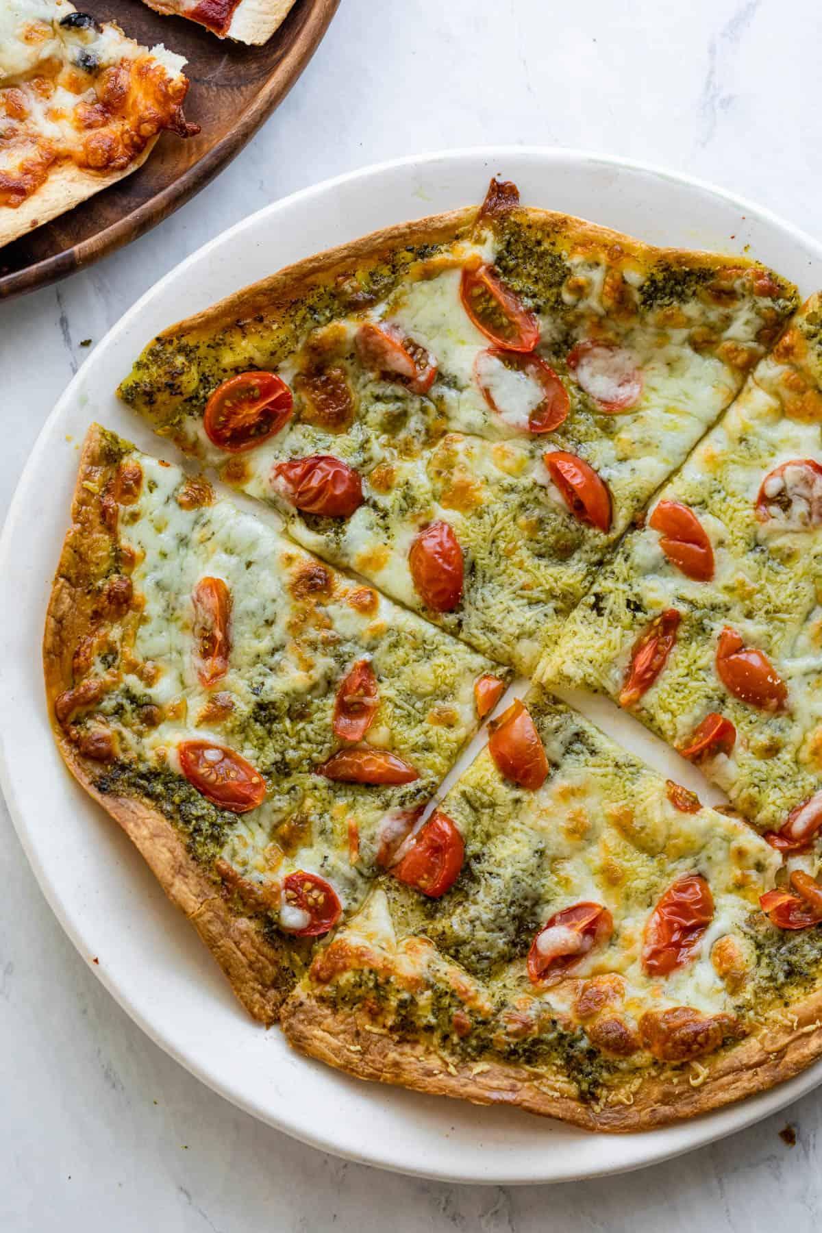 Pesto tortilla pizza sliced into four slices