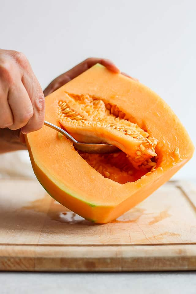 Removing seeds from cantaloup with spoon