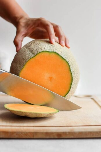 Cutting the top of cantaloupe with sharp knife