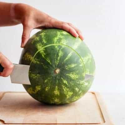 Large watermelon on cutting board with bottom part getting cut off