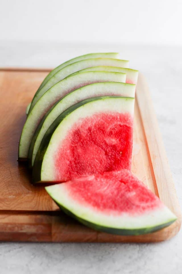 Sliced watermelon wedges with rind on cutting board
