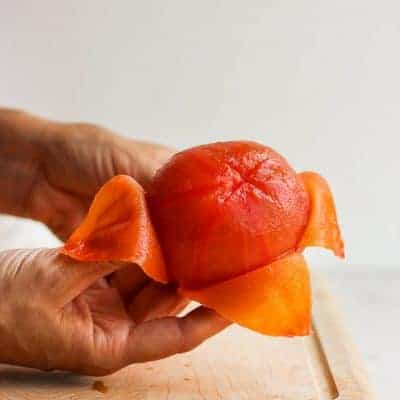 How to peel and seed a tomato - showing peeled tomato on cutting board
