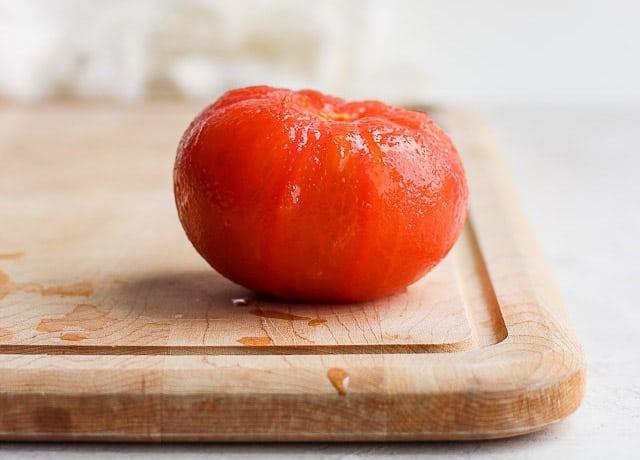Peeled large tomato on cutting board