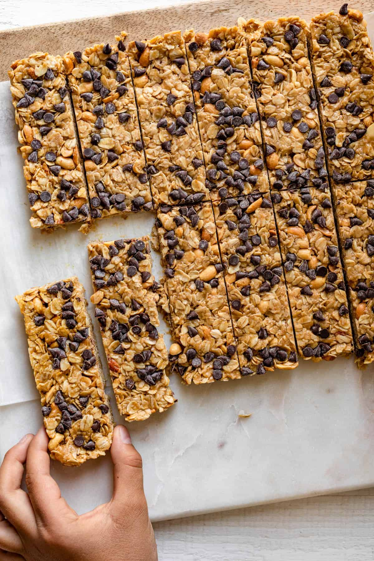 Chocolate Peanut Butter Granola Bars sliced with hand grabbing one