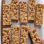 Honey nut cereal bars cut up on a board with parchment paper under