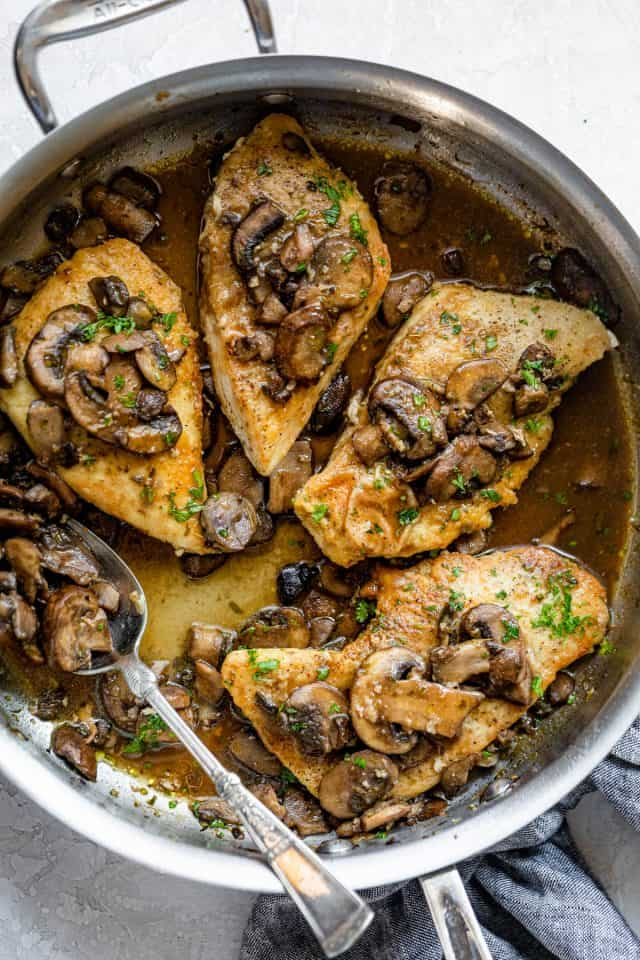 Sauteed chicken and mushrooms in a skillet with spoon inside for the sauce