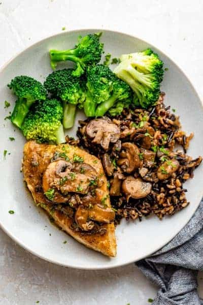 Plate of sauteed chicken with mushrooms, wild rice and broccoli
