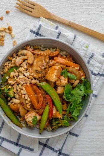 Thai peanut chicken stir fry serve in a bowl with brown rice