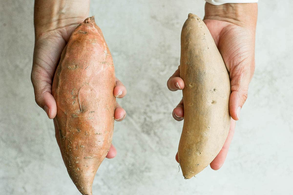 One hand holding sweet potato and another hand holding yam