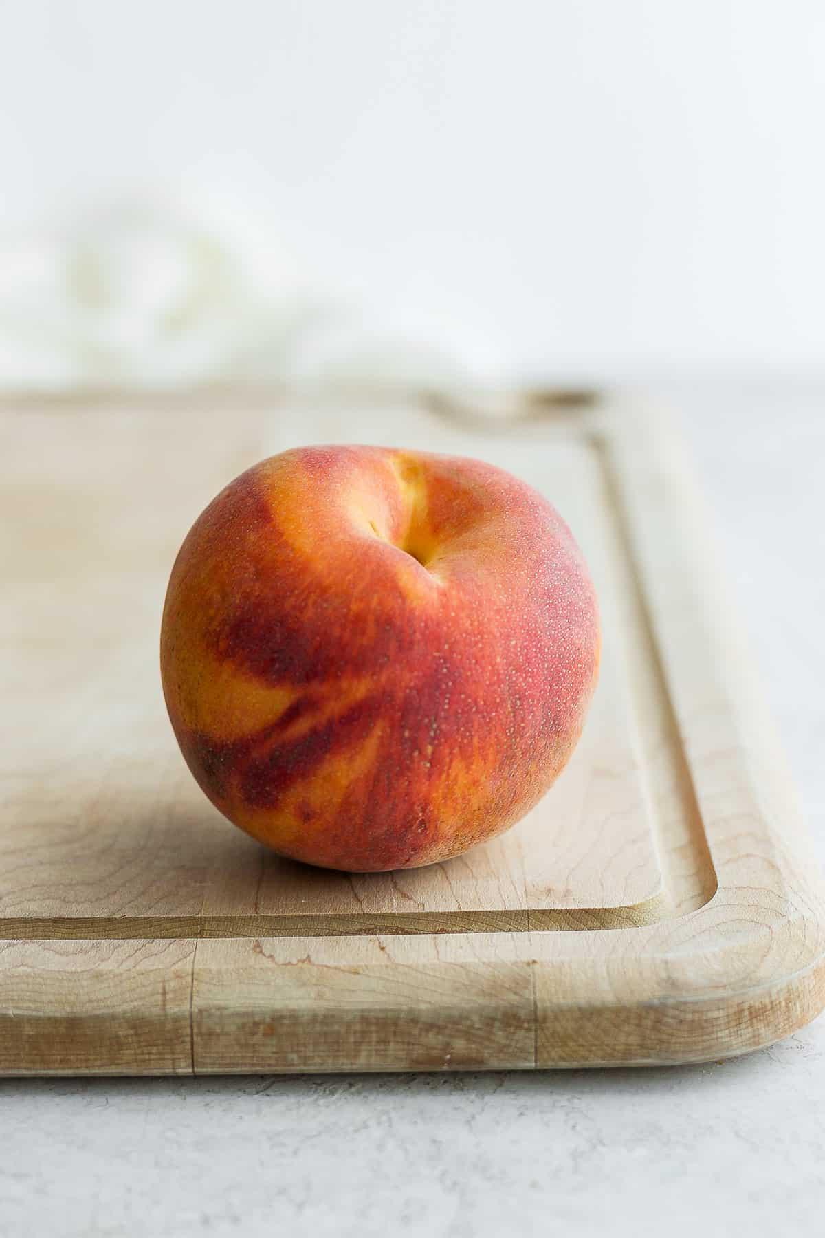One ripe peach sitting on cutting board