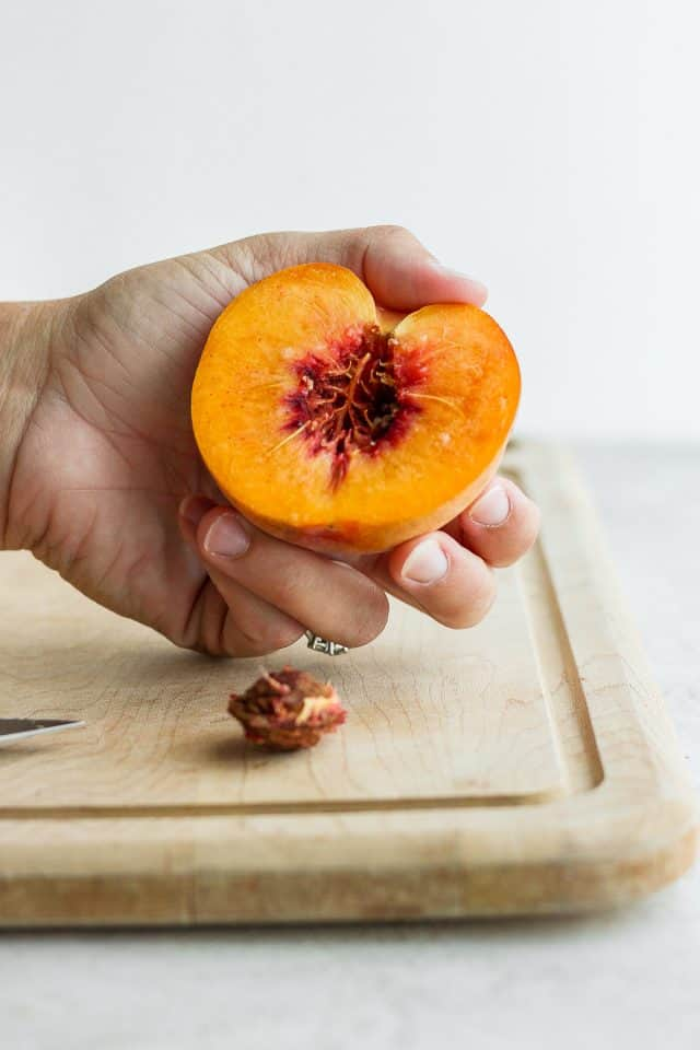Half peach cut with pit on the cutting board