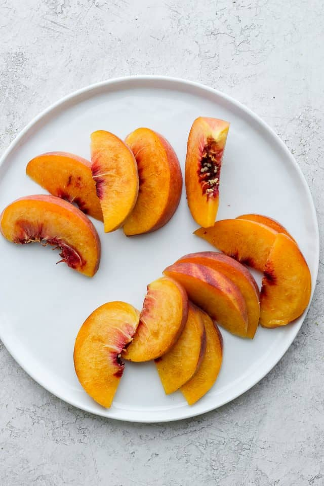Sliced peaches on white plate