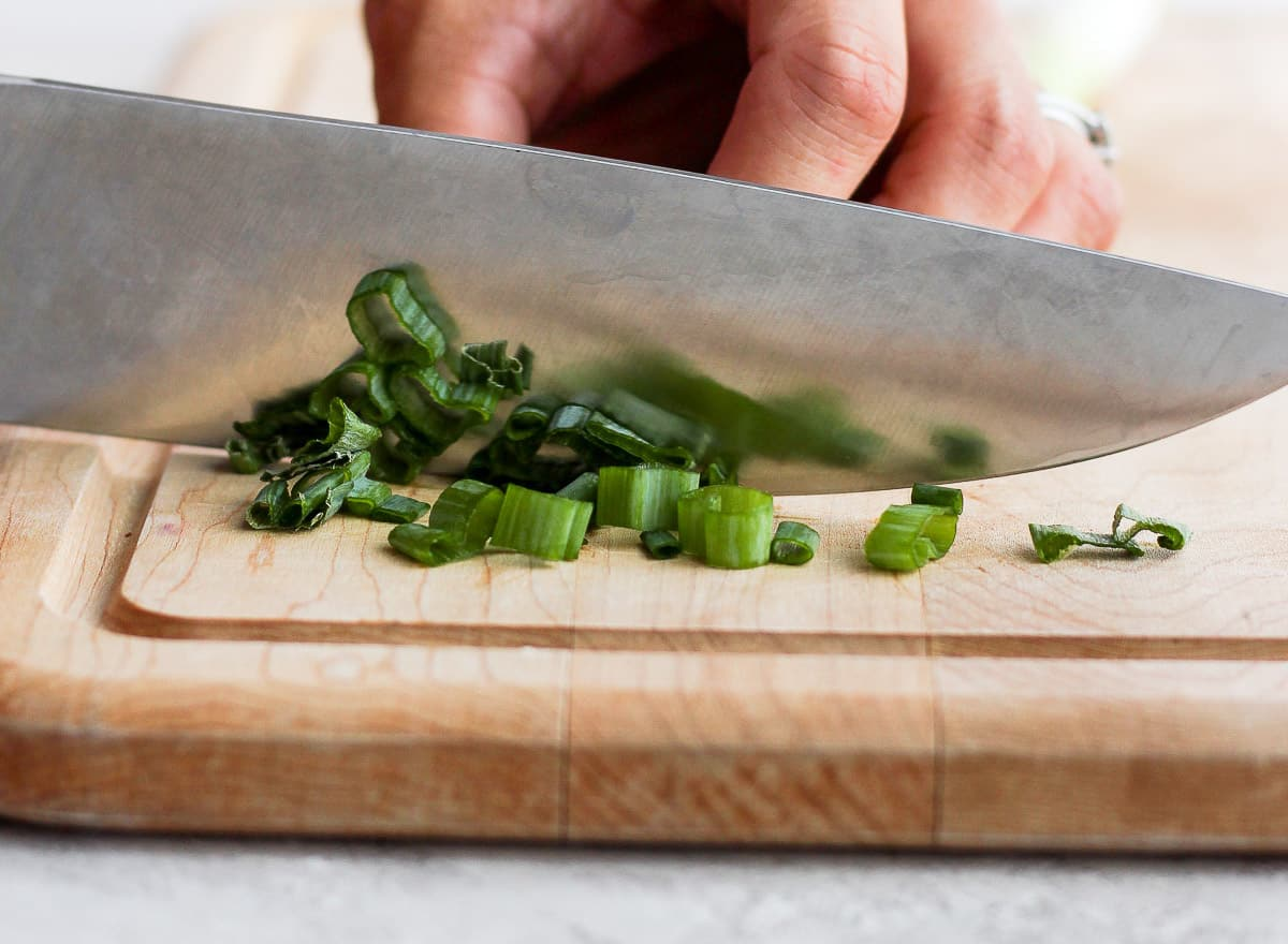 Chef's knife cutting green onions