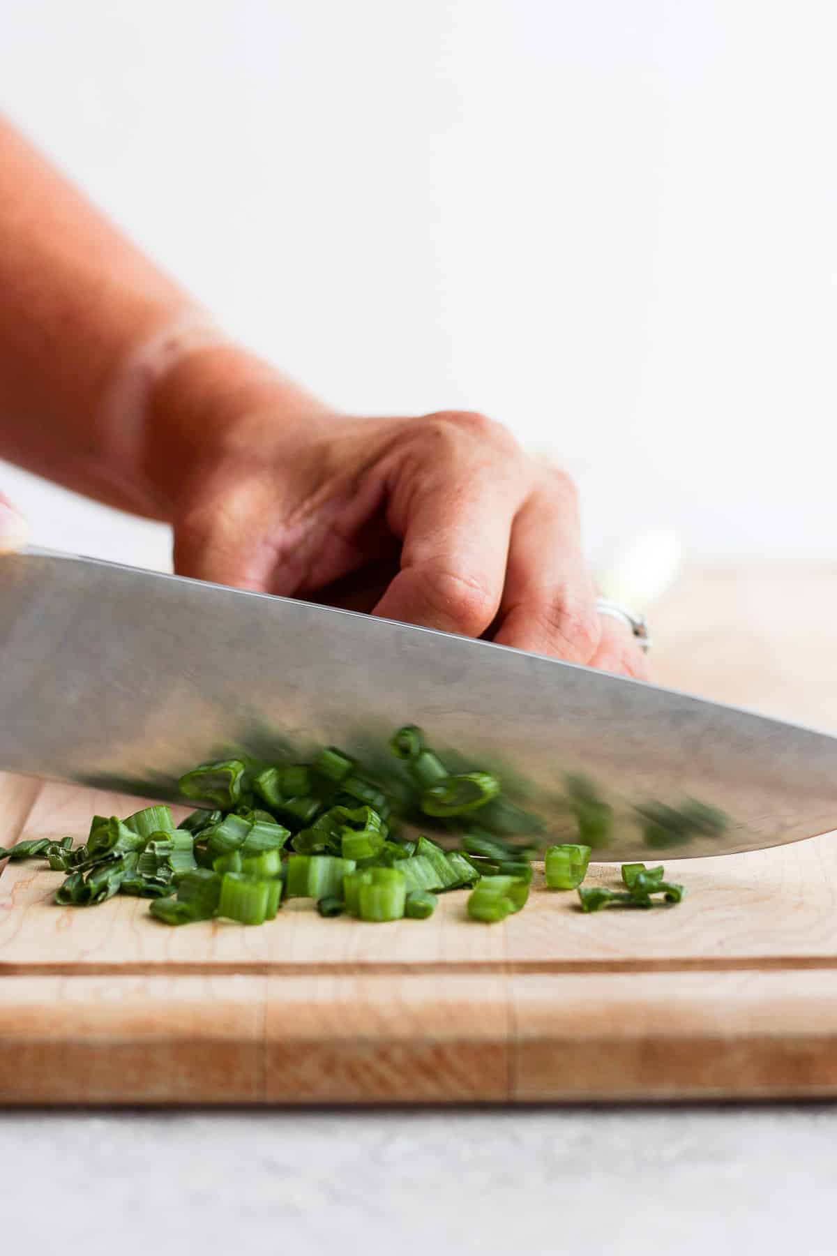 Chopping green onions on cutting board