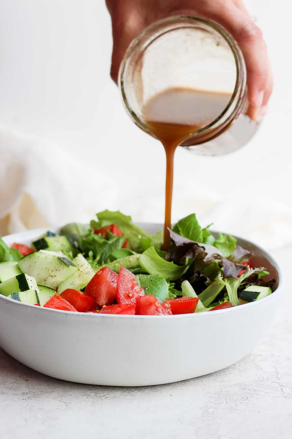 Homemade salad dressing getting poured over large bowl of salad