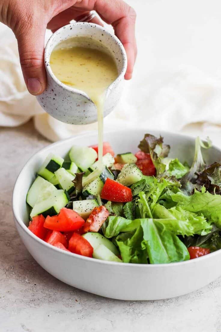 Homemade salad dressing getting poured over large bowl of salad