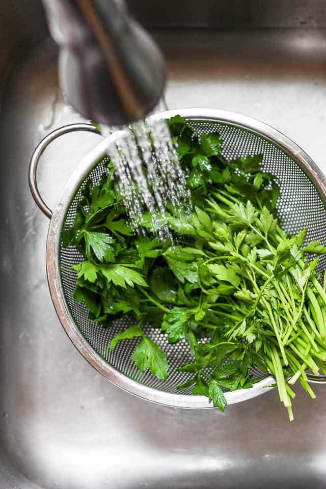 Bunch of parsley in colander getting rinsed with water in the sink