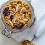 Homemade almond cranberry granola in a large glass jar