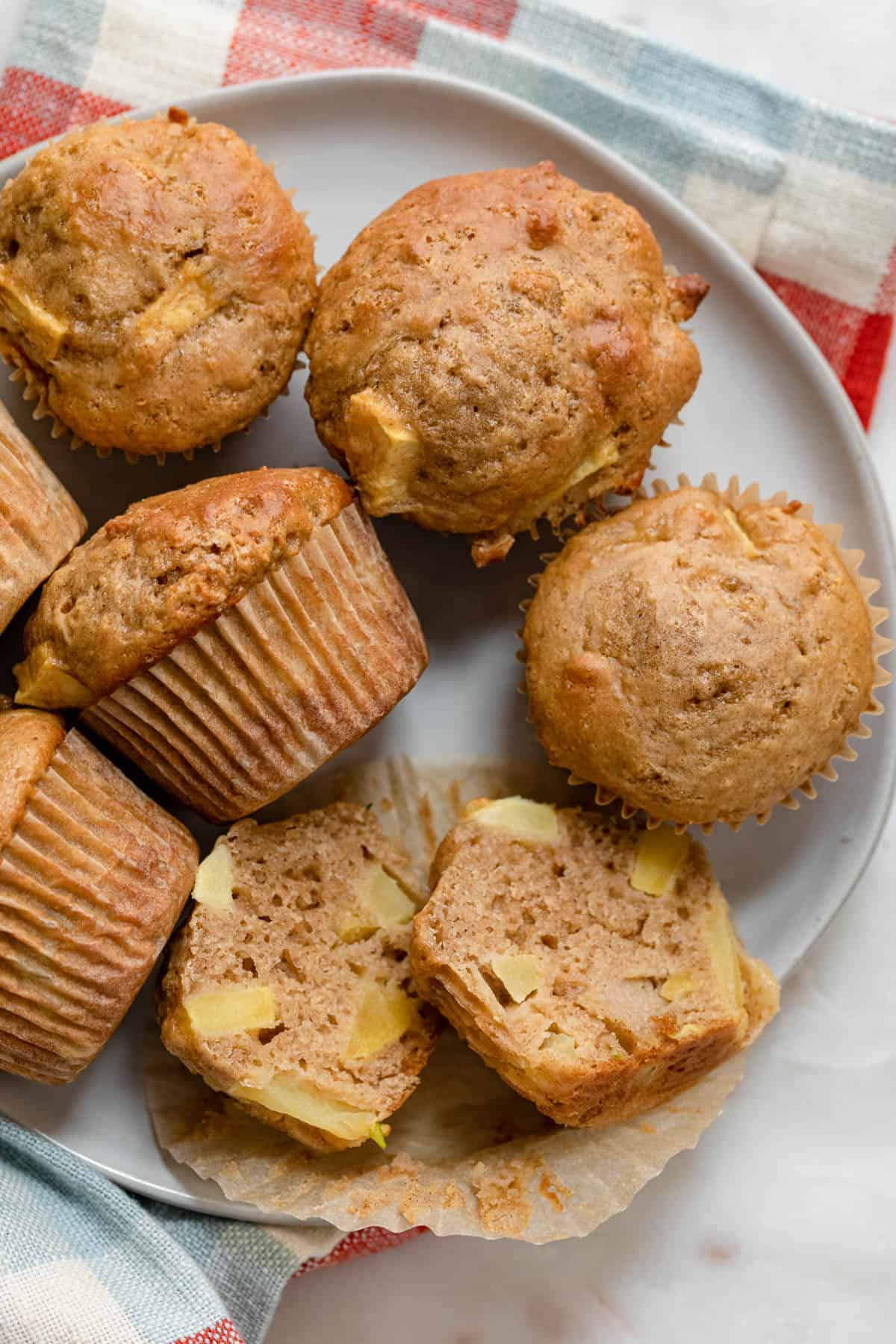 Plate of apple cinnamon muffins with one cut in half to show the apple pieces