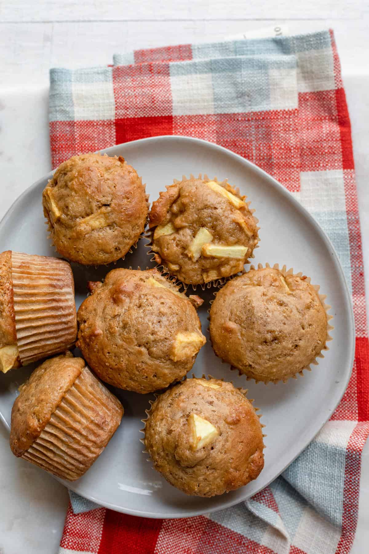 Apple cinnamon muffins on a plate with a red linen underneath