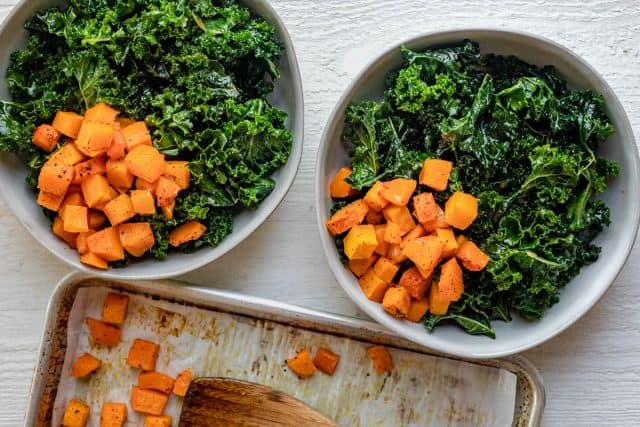 Showing how to assemble the grain bowl starting with kale and butternut squash in tow bowls