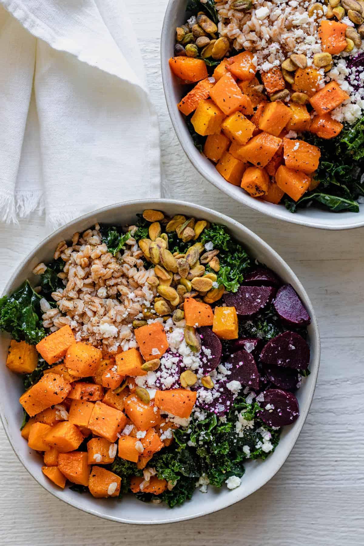 2 fall grain bowls made with butternut squash, kale, farro, beets, feta and pistachios