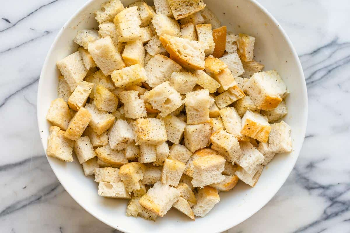 Sourdough bread cut into cubes in large bowl coated with oil and seasoning