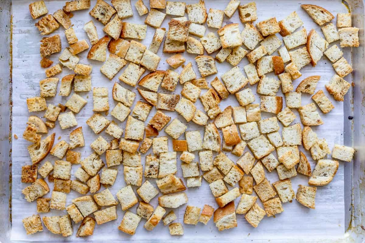 Croutons after baking on a baking sheet lined with parchment paper