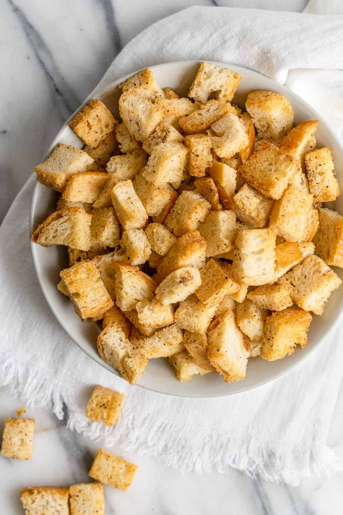 Homemade croutons in a large bowl with a couple fallen out