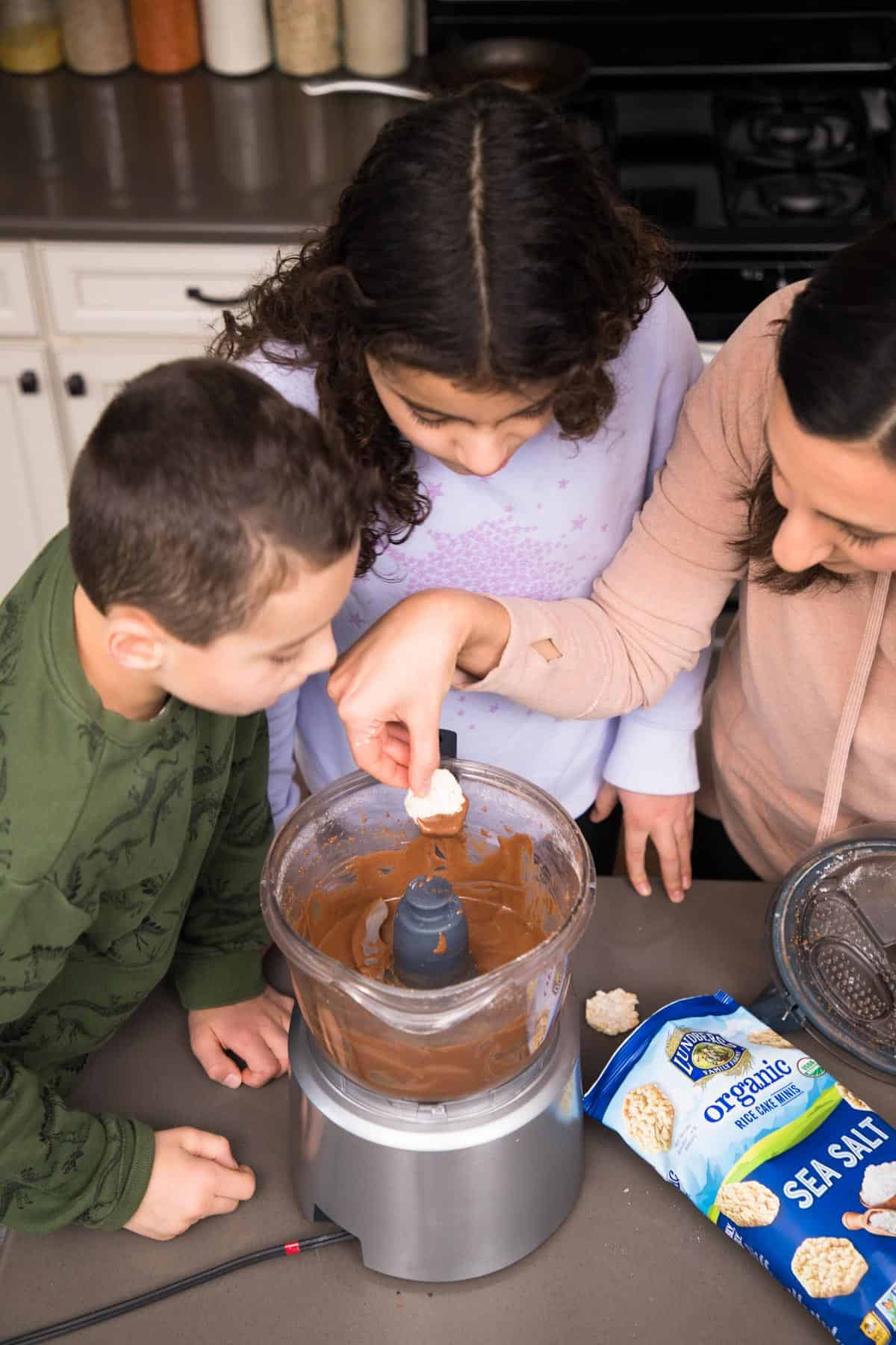 Yumna and kids dipping rice cake in nutella in food processor