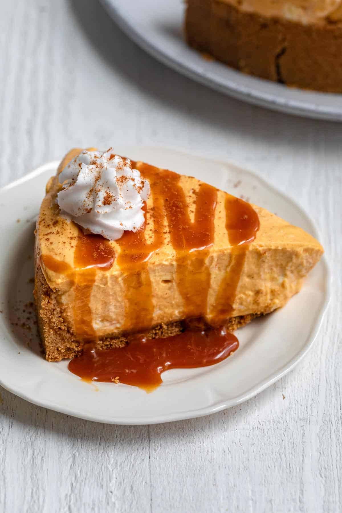 Slice of no bake pumpkin cheese with caramel on top and whipped cream