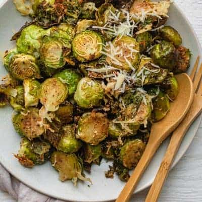 Parmesan brussel sprouts roasted in a large white bowl with a wooden spoon and wooden fork in bowl