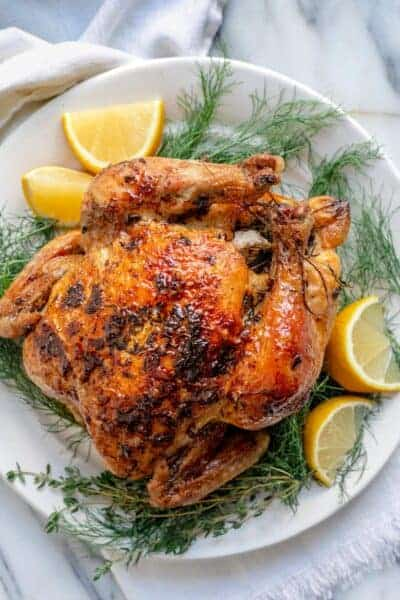White plate with roasted chicken with lemon and herbs