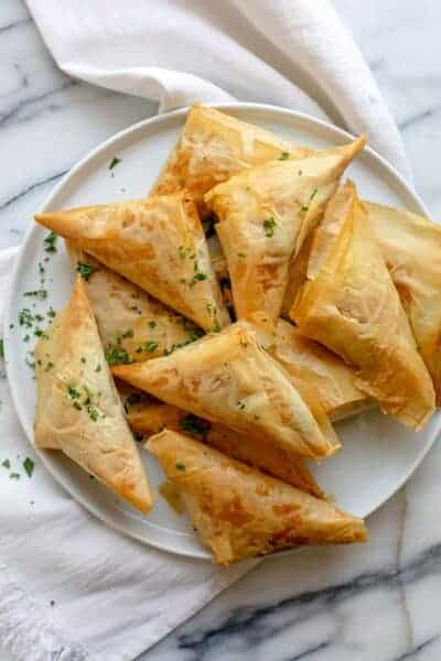 Greek spanakopita recipe made into triangles on a white plate