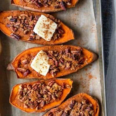 Small baking dish with four halves of sweet potatoes - two topped with dab of butter