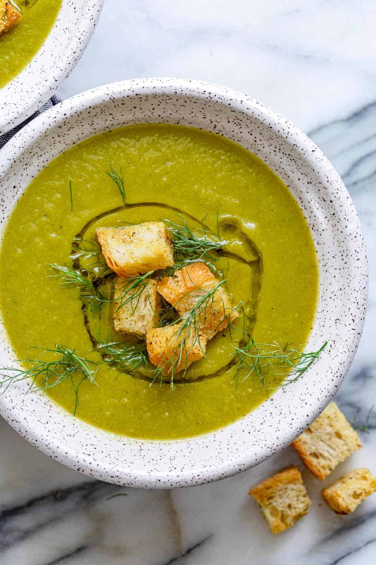 Large bowl of vegan broccoli soup with croutons on top