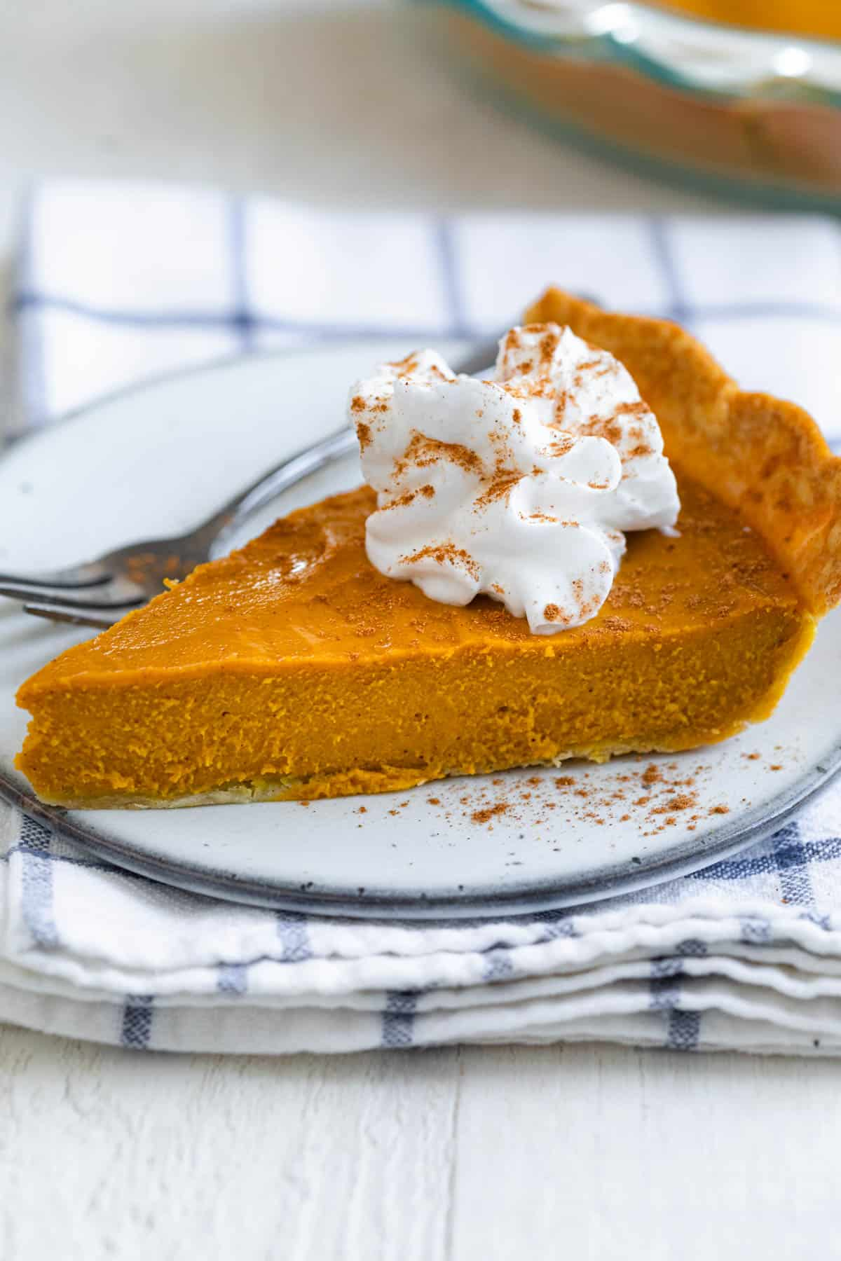 Slice of pumpkin pie on a small plate with whipped cream on top
