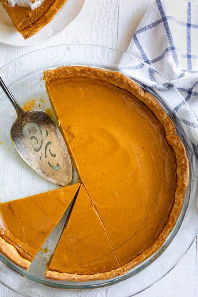 Pumpkin pie with slices cut out on a round glass baking dish