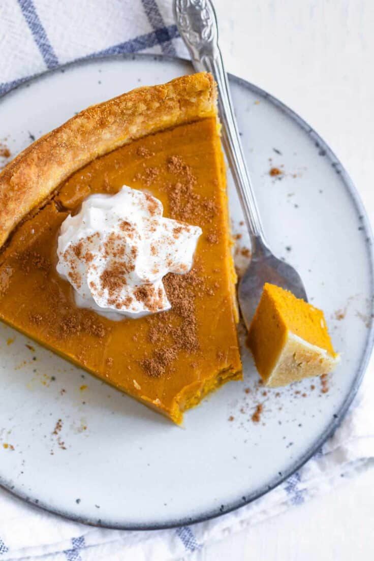 Plate of pumpkin pie with bite taken out