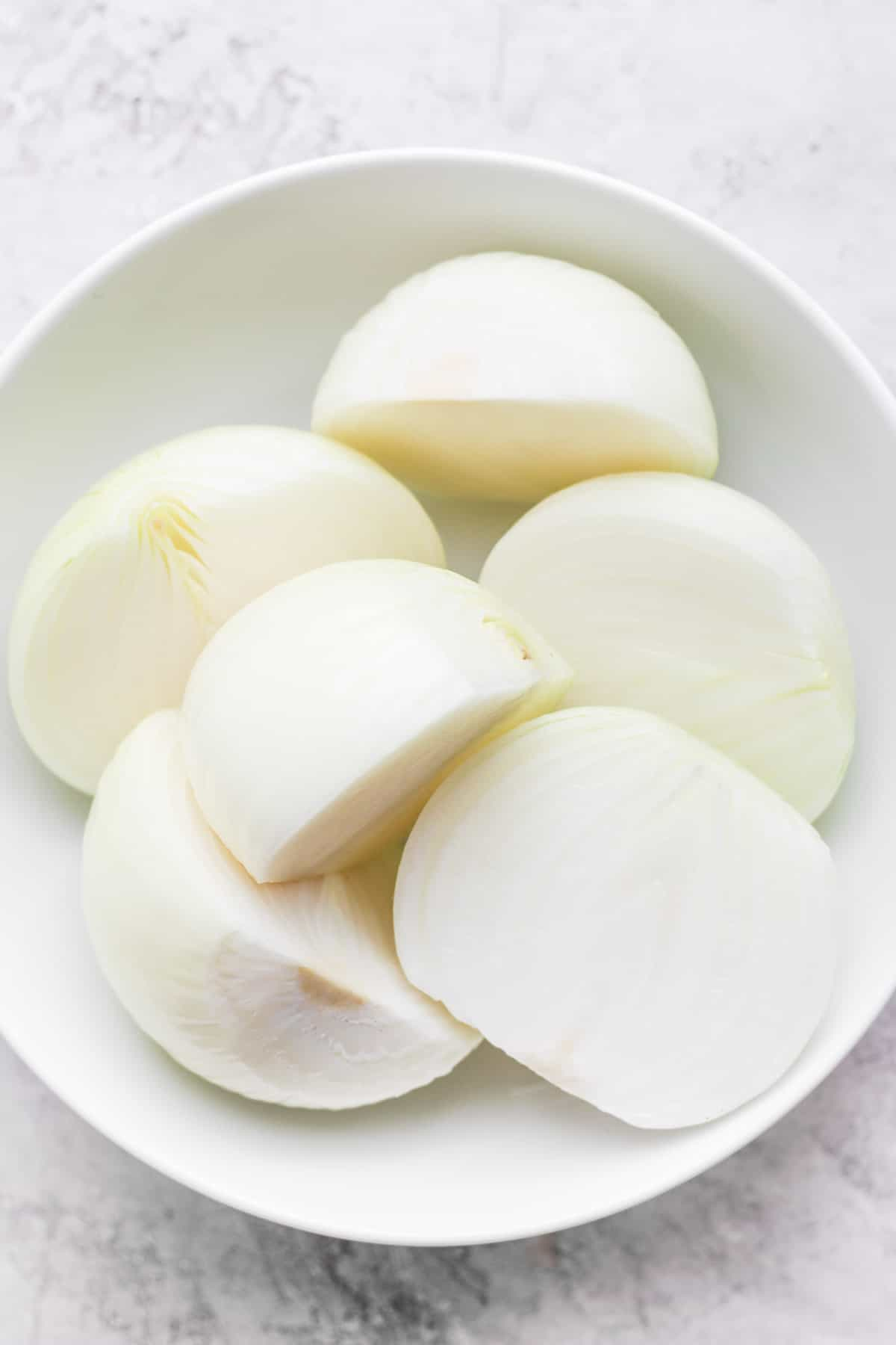 3 halves onions in a large white bowl